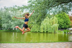 Beautiful brunette female fitness girl running and jumping exercising outside in a leafy and green city park. Lady in sports top jogging in park. Healthy girl lifestyle background with copy space