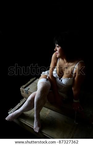 Beautiful brunette female in lingerie against black