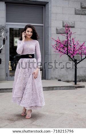 beautiful brunette female in long pink dress talking on the phone in the street