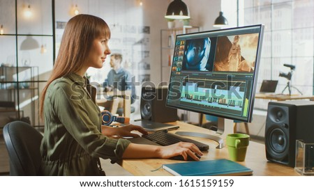 Beautiful Brunette Female Video Editor Works with Footage on Her Personal Computer with Big Display. She Works in a Cool Office Loft. Other Male Creative Colleague Walks in the Background. Stock photo ©