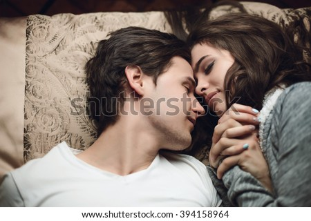 beautiful brunette girl and guy lying in bed and holding tightly hands. The concept of tenderness and affection #394158964