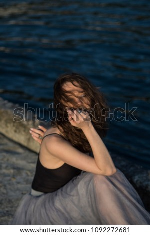 Beautiful brunette girl. By the sea. In a black T-shirt. With bare shoulders. In a gray-blue skirt. #1092272681