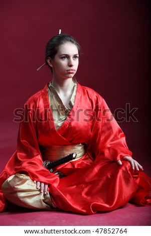 Beautiful brunette girl in a red kimono with a katana