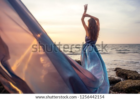 Beautiful brunette girl in blue gray chameleon dress with long train sitting on a beach at amazing sunset. woman in chic outfit near a rock on a tropical paradise island enjoying solitude and freedom #1256442154
