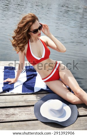 Beautiful brunette girl in good shape with long dark hair and tan skin red lips in fashion swimming suite hat lie seating near the pool beach river ocean with green water smile summer hot tan party