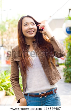 Beautiful brunette girl in jeans talking on the phone in  the  city at outdoors
