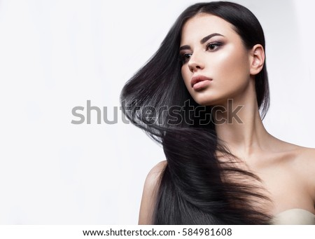 Beautiful brunette girl in move with a perfectly smooth hair, and classic make-up. Beauty face. Picture taken in the studio on a white background. #584981608