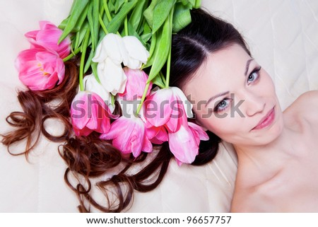 Beautiful brunette girl laying in bed with tulip flowers