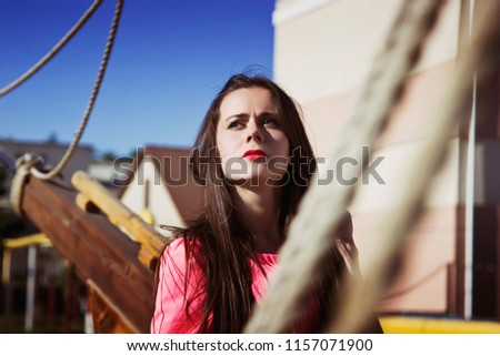 Stock Photo Beautiful brunette girl looks at the expanses under a blue sky