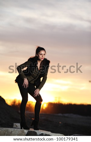 Beautiful brunette girl posing at sunset
