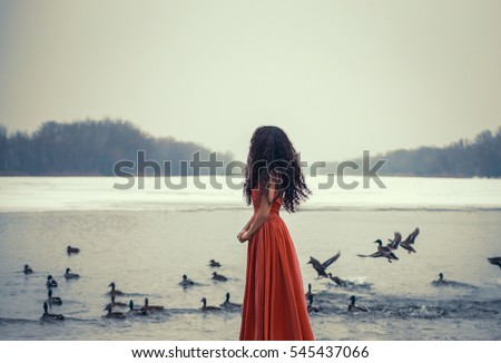 Beautiful brunette girl standing with her back to the camera and looking at the birds. Background shore of a frozen river. She is wearing a beautiful orange dress. Fantasy photo, creative color.