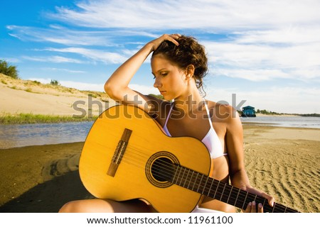 Beautiful brunette girl wearing white swimsuit with a guitar at the beach, with blue sky and white clouds at background