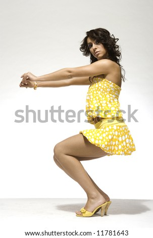 beautiful brunette girl wearing yellow clothes on light background