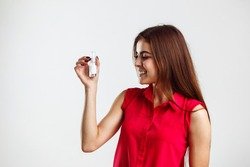 Beautiful brunette girl wears red shirt holds bottles of parfumes with copyspace on white isolated background