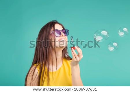 Beautiful brunette girl wears sunglasses making soap bubbles on blue background