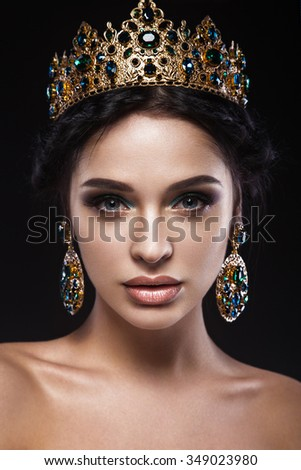 Beautiful brunette girl with a golden crown, earrings and professional evening make-up. Beauty face.  #349023980