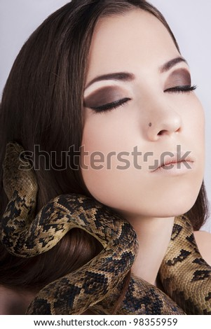 beautiful brunette girl with a snake around her head and closed eyes