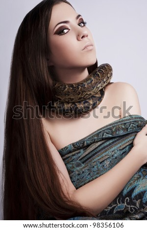 beautiful brunette girl with a snake around her neck looks at the viewer