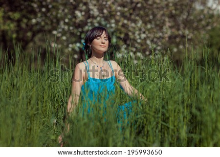 Beautiful brunette girl with closed eyes sitting in a meadow in the grass and meditating.