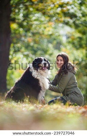 Beautiful brunette girl with her Dog in Autumn park. Bernese Mountain Dog. Woman with dog in autumn outdoors. Friendship in fall. Girl hugging and embracing her dog.