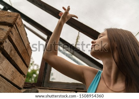 Beautiful brunette girl with natural healthy skin touches the roof window with her finger, listening to the sound of rain with closed eyes, summer rain