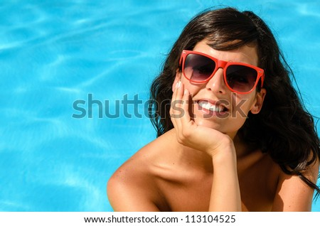 Beautiful brunette happy face looking cheerful at camera in a pool on blue water background. Summer hot day in pool with caucasian smiling model.