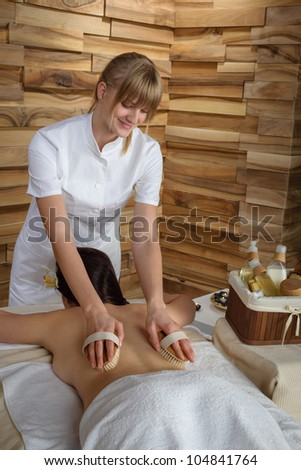 Beautiful brunette having wooden brush massage at luxury spa