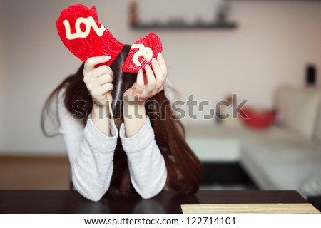 Beautiful brunette holding two parts of broken heart
