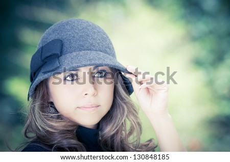 Beautiful brunette in hat on green park background - stock photo