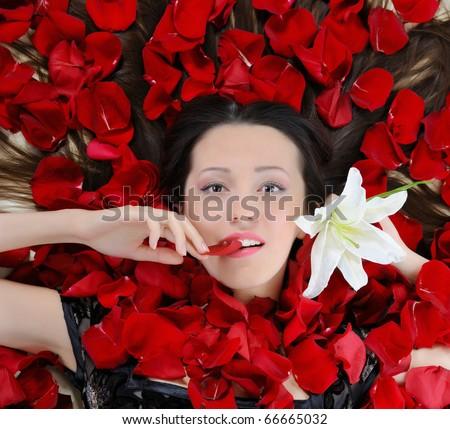 beautiful brunette in rose petals - stock photo