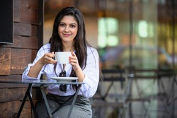Beautiful brunette Indian american woman sipping cappuccino on coffee shop cafe patio, smiling relaxed with mug cup