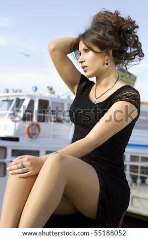 beautiful brunette lady in black dress on mooring