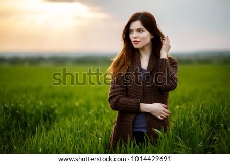 Beautiful brunette lady in wheat field at sunset. Happy beautiful woman in meadow. Beautiful carefree woman in fields
