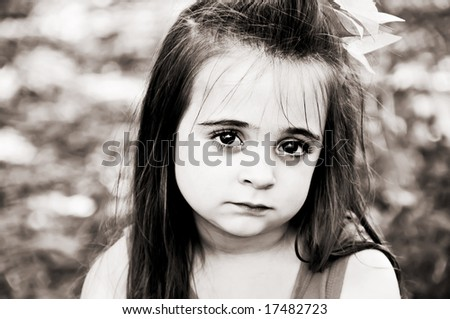 Beautiful brunette little girl posing with a sad facial expression in brown tones