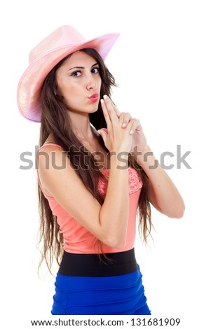Beautiful brunette longhaired woman with pink cowboy hat. Pointing with fingers like a gun, simulating blowing the gun-smoke away. Isolated on white.