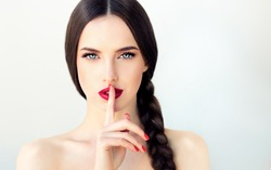Beautiful  brunette model girl with  long braid hair . Hairstyle  pigtail  . Red lips and nails manicure .Woman  holds a finger on her mouth a secret