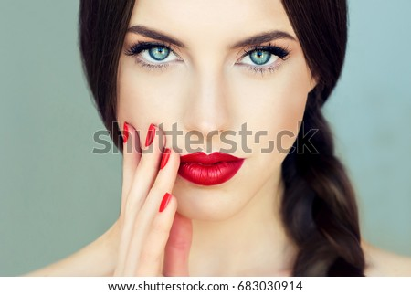 Beautiful  brunette model girl with  long braid hair . Hairstyle  pigtail  . Red lips and nails manicure .