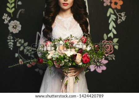 Beautiful brunette model woman with stylish hairstyle in the stylish lace dress holding a big luxury bouquet of exotic flowers in her hands, posing at black background