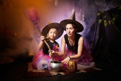 Beautiful brunette mother and cute little daughter looking as witches in special dresses and hats conjuring with a pot in room decorated for Halloween. Halloween style photo shoot