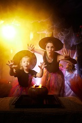 Beautiful brunette mother and cute little daughter looking as witches in special dresses and hats conjuring with a pot in room decorated for Halloween. Halloween style photo shoot.