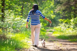 Beautiful brunette on the walk with the dog
