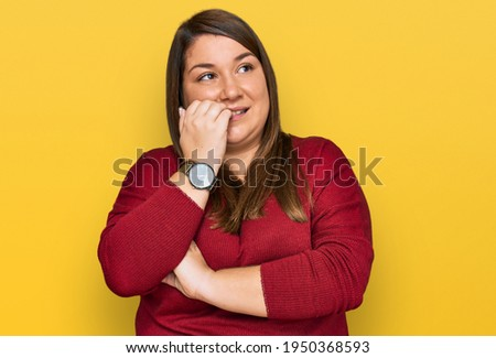 Beautiful brunette plus size woman wearing casual clothes looking stressed and nervous with hands on mouth biting nails. anxiety problem.  Foto stock ©