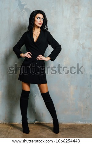 Beautiful brunette posing against a background of vintage wall texts in an interior studio. Black clothes are high shoes. #1066254443