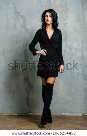 Beautiful brunette posing against a background of vintage wall texts in an interior studio. Black clothes are high shoes. #1066254458
