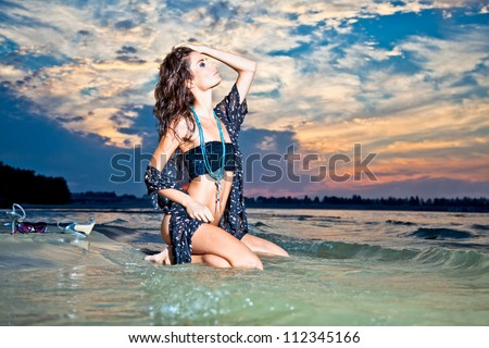Beautiful brunette posing  on river bank in sunset. Art photo.