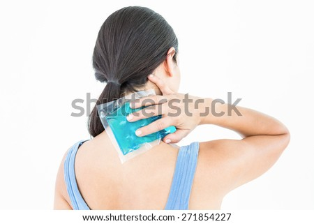 Beautiful brunette putting gel pack on neck on white background