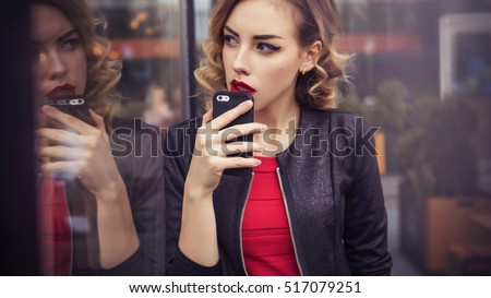 Beautiful brunette sexy spy agent (killer or police) woman in leather jacket and red luxury dress with a phone in her hand watching after someone, make business work phone calls in european city #517079251