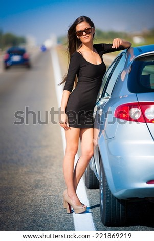 beautiful  brunette  sexy  woman in black dress and sunglasses  has the broken car and  long hair  and elegant body