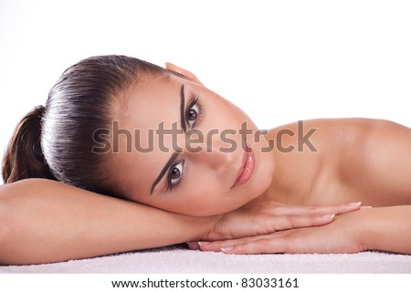 Beautiful brunette spa woman lying on towel in spa salon