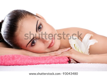 Beautiful brunette spa woman lying on towel in spa salon
